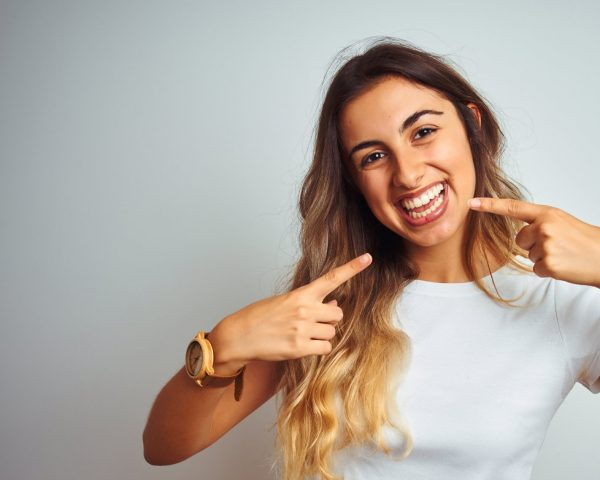 Young beautiful woman wearing casual white t-shirt over isolated background smiling cheerful showing and pointing with fingers teeth and mouth. Dental health concept.
