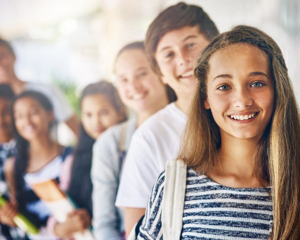 Portrait of a group of happy schoolchildren standing in a line outside their classroom